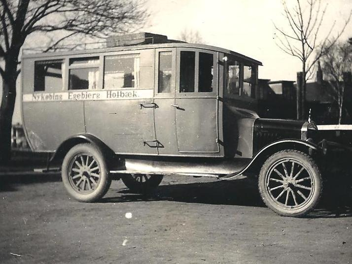 En Ford tilhørende Ludvig Nielsen, Abildøre, var en af de første busser på ruten til Holbæk, der kørte via Egebjergvej, og den er her fotograferet over for Holbæk station engang i 20´erne ved OHJs kontorbygning. Foto: SCO