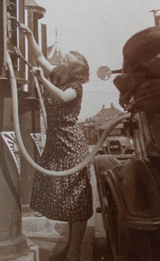 Billedet er fra 1929 og taget ud for på Algade. Apotekets karakteristiske spir ses i baggrunden.  Det er datteren Marie Louise Larsen der som 16 årig passer tanken.